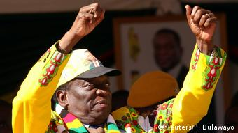 Emmerson Mnangagwa, wearning a yellow shirt and a cap, raises his arms