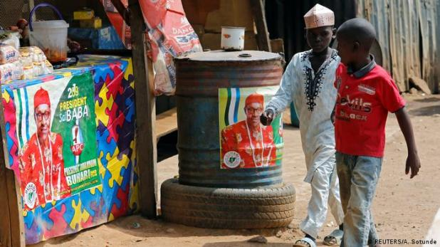 Two young boys in Nigeria walk past a stall covered in election posters supporting Muhammadu Buhari