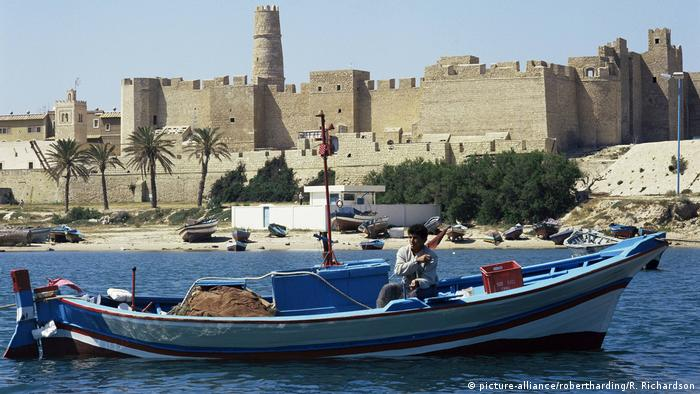 A man sits in a small boat on a stretch of water with a towering fortress in the background