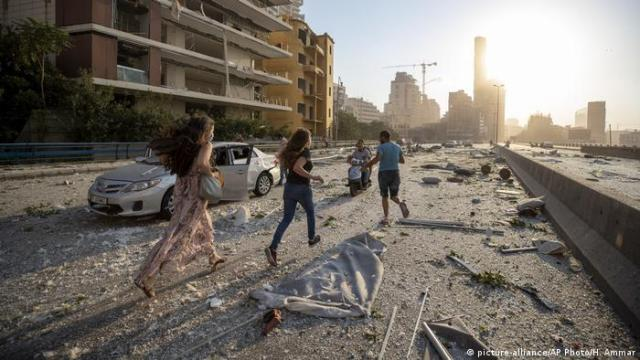 People in Beirut run through the rubble in the explosion aftermath | Gewaltige Explosion in Beirut (picture-alliance/AP Photo/H. Ammar)