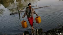 A Myanmar woman fetches water from a small pond