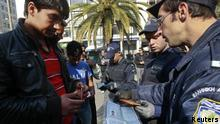 Greek police go through immigrants' documents