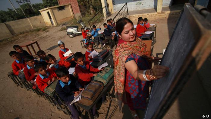 Indian school children attend a class in the open at a government school in the outskirts of Jammu, India
