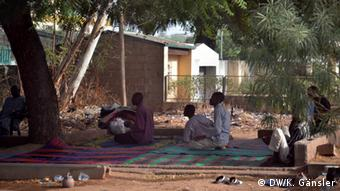 Muslim faithfuls kneeling in prayer on a mat in a public place.