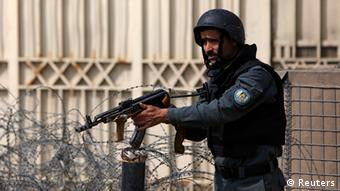 An Afghan policeman takes position near an election commission office during an attack by gunmen in Kabul March 29, 2014.