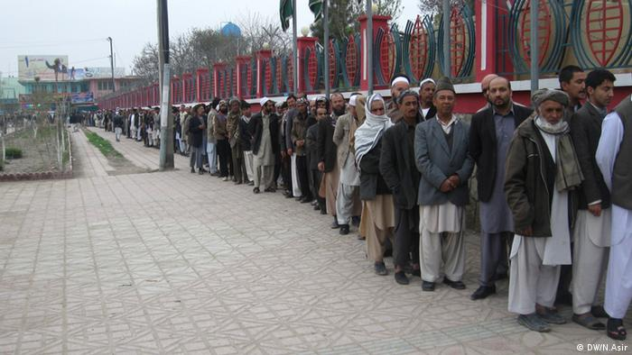 Men queue along side a red and green fence (Foto: N.Asir-DW)