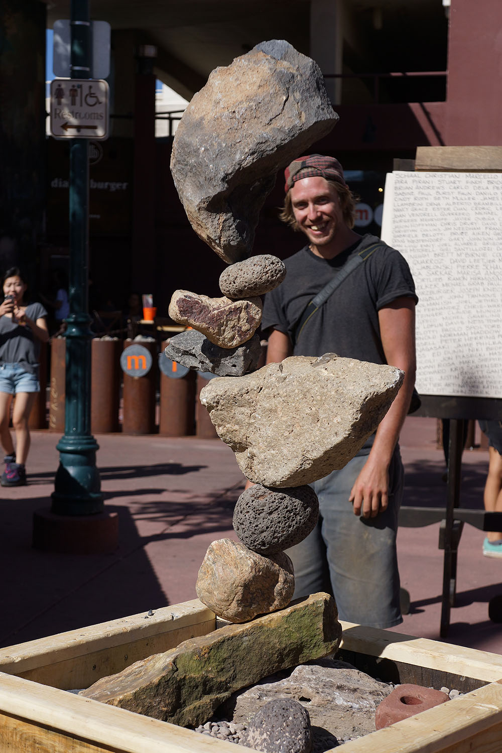 Michale Grab stands behind one of his gravity-only stone sculptures. Flagstaff Square, Sept. 2014.