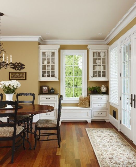 Rich gold walls are complimented with white cabinets and warm woods
