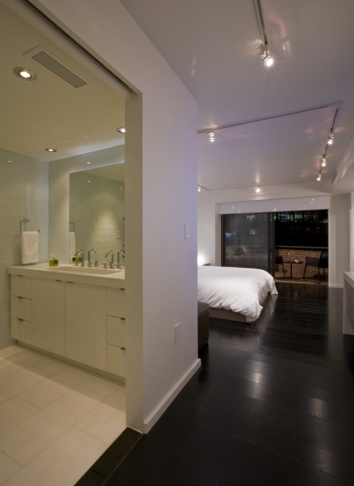 master bath and bedroom, with expanse of dark wood flooring