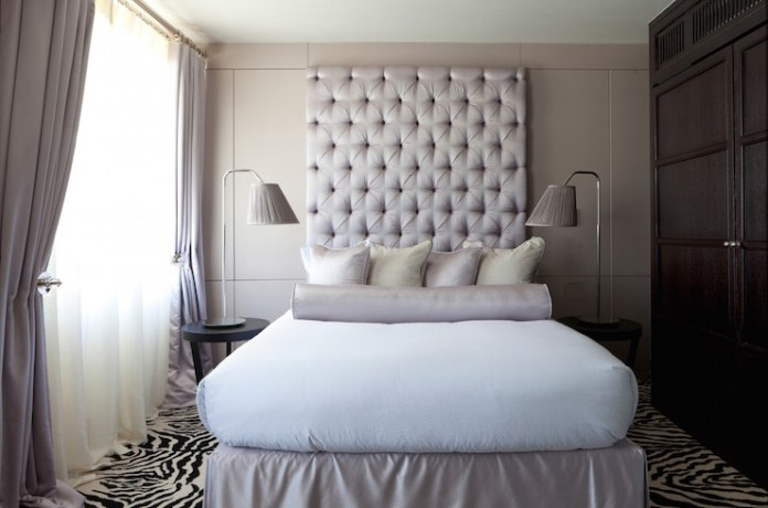 tall-tufted-gray-headboard-gray-bedskirt-zebra-rug