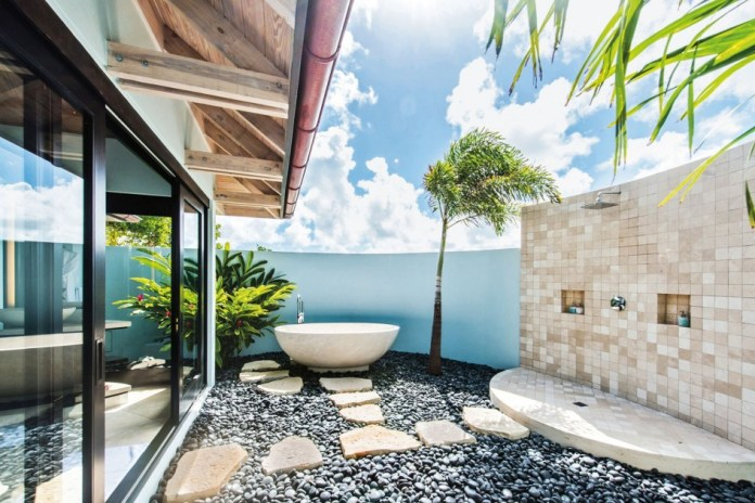 Luxury Tropical Outdoor Shower with white bathtub and pebble Stone flooring connected with indoor bathroom.