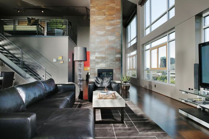 Luxurious modern living room in loft apartment with a classic view and a large leather sofa brings the best comfort with modern amenities and compelling grey hardwood flooring.