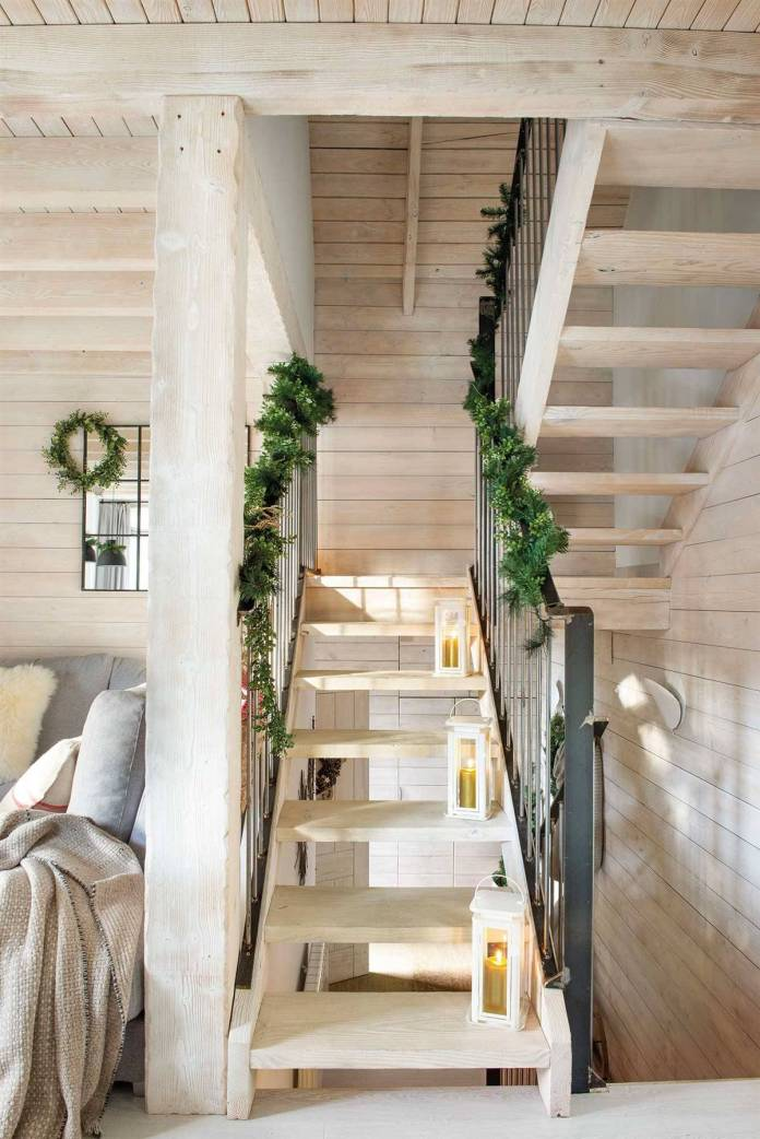 STAIRCASE DECORATED FOR CHRISTMAS WITH LANTERNS AND A PINE GARLAND