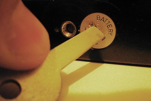 Chave abrindo a tampa de bateria de câmera analógica