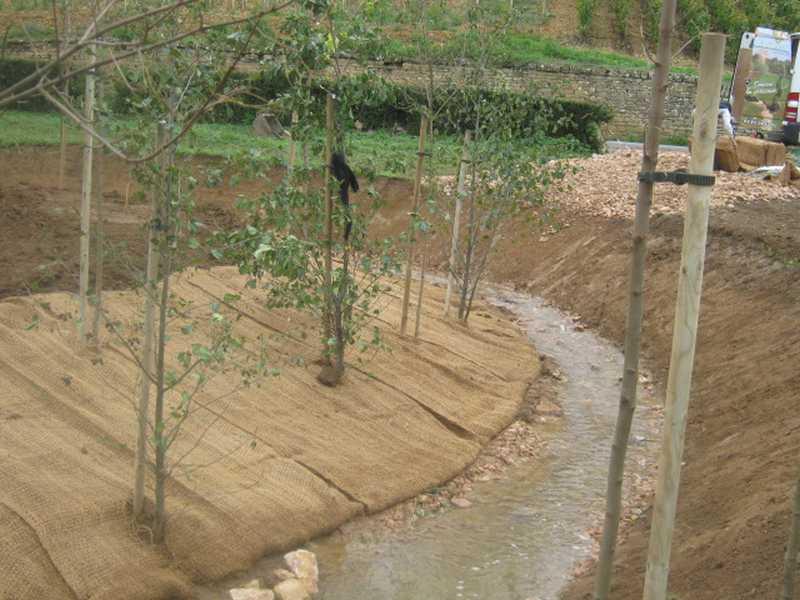 Vue de la Denante en chantier : le textile coco est posé, les nouveaux arbres plantés.