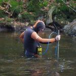 Loïc en combinaison prend des mesures de courant de la rivière