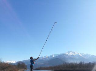 Benoît réalise un quadra de végétation à l'aide d'une perche et d'un appareil photo pour le suivi scientifique et technique des bancs de l'Isère
