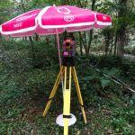 Le tachéomètre sous un parasol pour le protéger de la pluie
