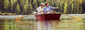 couple floating on lake in wooden boat