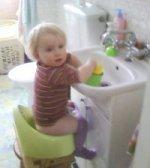 Kinga na nocniku bawi się w umywalce.