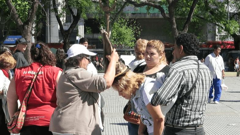 Fig. 5 Imposición de una pequeña figura de plástico sobre la cabeza de una mujer, Plaza Miserere (Buenos Aires), festividad de Todos los Santos, 31 de octubre 2014.