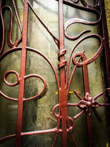 The curves of the wrought iron railing softens the composure of the austere architecture