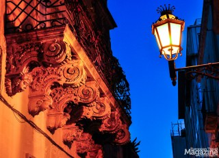 The golden streetlights play with the Baroque motifs