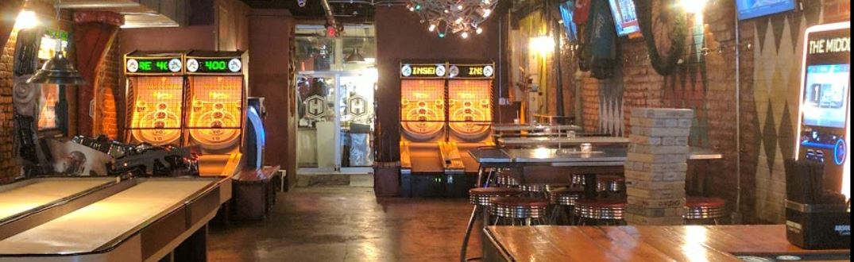 Game room in restaurant with skeeball, jukebox and shuffleboard