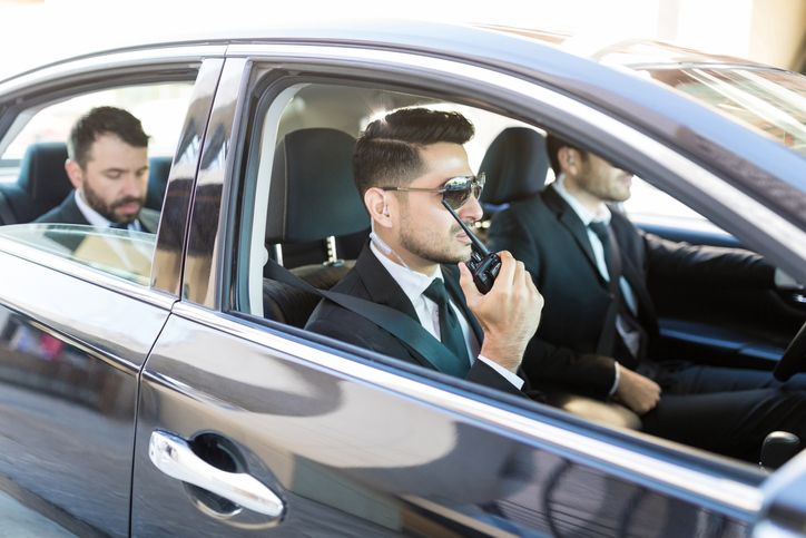Two security drivers with executive in backseat