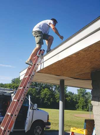 Volunteers from Avery Renovations cut plywood to board up the Liverpool Girls Softball League's concession stand to secure the building after an arson fire on July 2 caused significant damage to the facility. Since the fire, donations have poured in from all over the community.