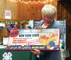 Retiring CCE-MC team member Debbie SeGuin, pictured, was honored for her more than 30 years of service to the organization and given a vintage New York farmers market sign as a gift during the CCE-MC annual meeting on Dec. 4. (photo by Jason Emerson)