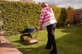 Lady mowing her lawn in the sun