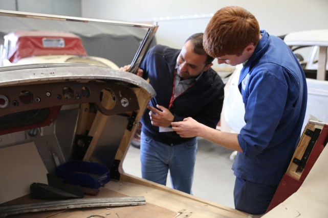 Earley Engineering apprentice Matt shows a visitor one of the current projects in the bodyshop