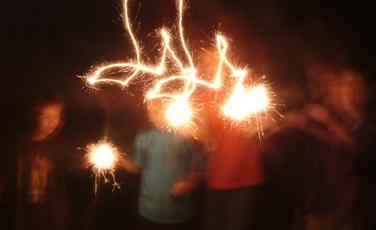 boys waving sparklers in dark