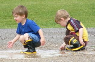 toddlers splashing in water of mud puddle