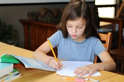 girl working at desk on school papers