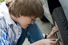 boy removing lugnut from wheel