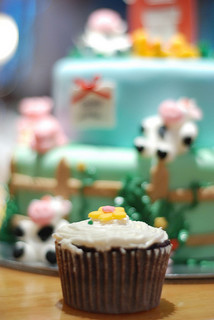 birthday cupcake sitting in front of well-decorated cake
