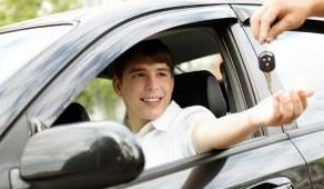 teen boy smiling in driver's seat as adult hands him car keys