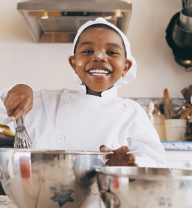 cheery boy cooking with flour on his nose