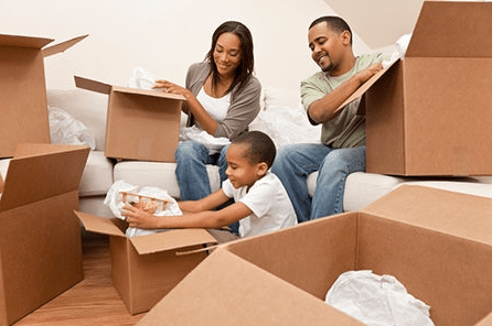 mother, father, and son packing moving boxes
