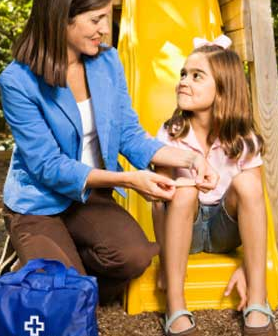 girl sitting on slide while mom puts band aid on knee