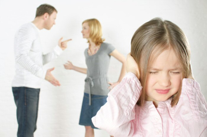 parents arguing while daughter is holding hands over her hears and wincing