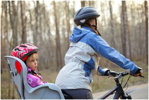 woman riding bike with daughter riding in child seat