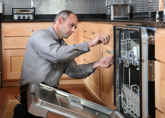 man working on installing a dishwasher
