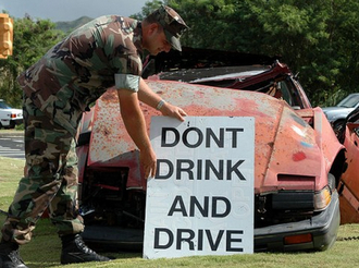 soldier placing sign that says don't drink and drive in front of wrecked car