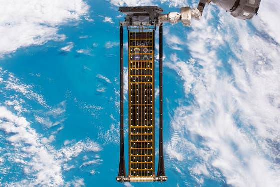The Roll-Out Solar Array Attached to a Robotic Arm of the ISS