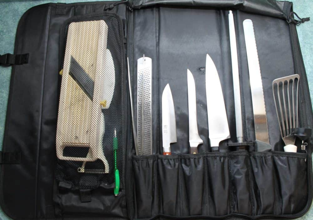 A black knife roll with a variety of knives and other tools