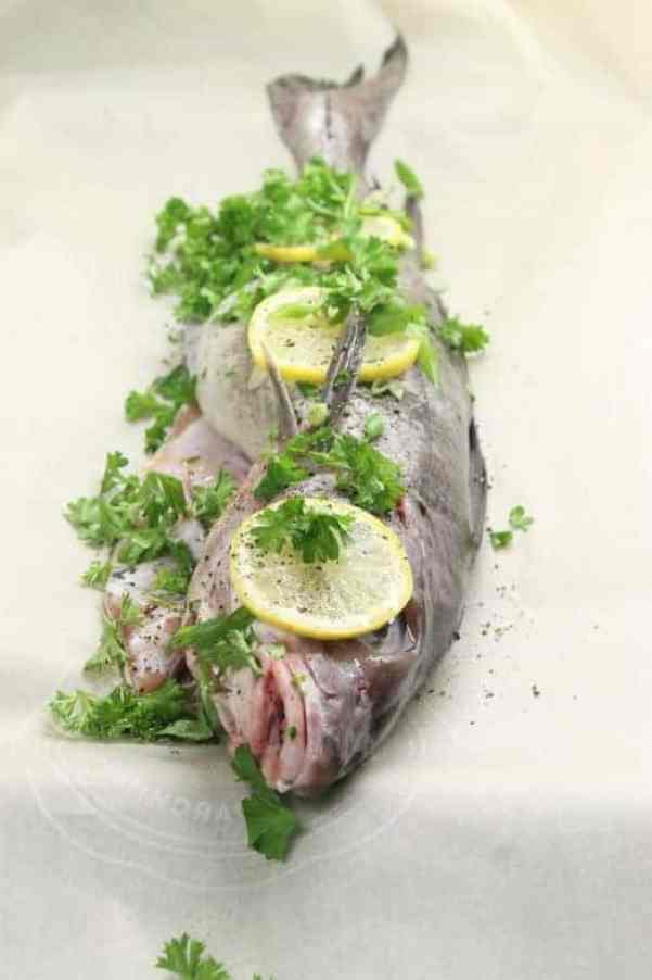 Prepping whole baked haddock for the oven.
