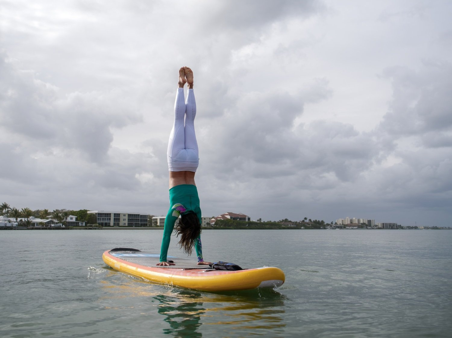 girl doing a handstand on an inflatable SUP